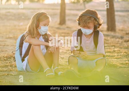 Zwei Kinder mit Schultaschen und Masken sitzen in der Woods hören Musik mit drahtlosen Helmen auf ihrem Handy Telefone - Stockfoto