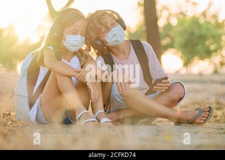 Zwei Kinder mit Schultaschen und Masken sitzen in der Woods hören Musik mit ihren Köpfen zusammen und emotional Expression mit kabellosen Kopfhörern, die mit ihren Mobiltelefonen verbunden sind - Stockfoto