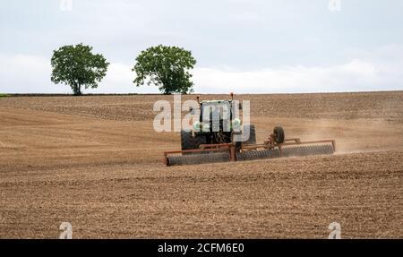 Bauer pflügt ein Feld mit seinem Traktor mit einer Rolle und Presse ausgestattet, um den Boden vor dem Pflanzen vorzubereiten. Zwei Bäume im Hintergrund isoliert. - Stockfoto