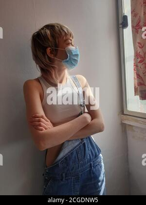Mädchen isoliert und allein zu Hause tragen medizinische Maske - Stockfoto