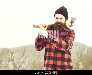 Gutaussehender Mann oder Holzfäller, bärtiger Hipster, mit Bart und Schnurrbart in rot kariertem Hemd Spaziergänge mit Axt im verschneiten Wald am Wintertag im Freien auf natürlichem Hintergrund - Stockfoto