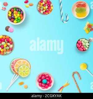Lutscher und Bonbons. Bunte Süßigkeiten, festliche Dekoration. Bunte Bonbons auf hellblauem Hintergrund, Draufsicht mit Platz zum Mitmachen oder Begrüßen - Stockfoto