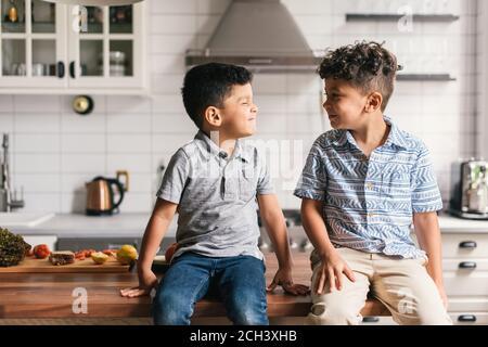 Zwei Jungen auf stilvolle Küchentheke machen lustige Gesichter an Einander