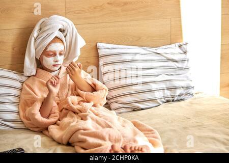 Adorable kaukasischen Kind Mädchen in Maske kümmert sich um sich, sie sägt Nägel mit einer Datei, wollen schön sein. Haben Ruhe zu Hause, nach dem Bad Stockfoto