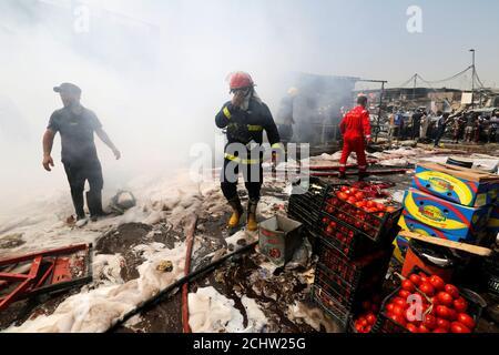 Ein Feuerwehrmann inspiziert den Ort eines Autobombenanschlags auf dem Markt von Jamila im Stadtteil Sadr City in Bagdad, Irak, 28. August 2017. REUTERS/Wissm al-Okili Stockfoto
