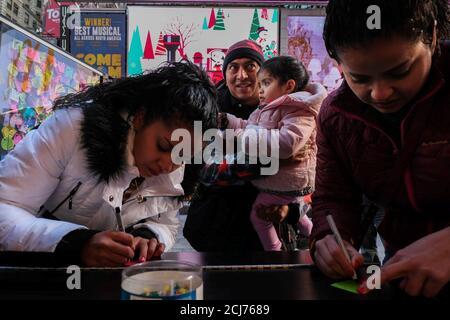 Eine Familie von Touristen schreiben ihre Neujahrswünsche auf Post-it-Notizen, die als Konfetti während der Times Square Silvesterfeier in New York, USA 5. Dezember 2019 verwendet werden. REUTERS/Gabriella N. Baez - Stockfoto