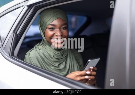 Lächelnde Schwarze Muslimische Frau Sitzt Auf Dem Rücksitz Im Auto, Mit Smartphone Stockfoto