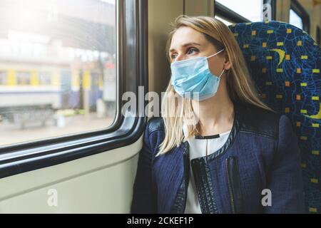 Frau mit Sicherheit Gesichtsmaske sitzt im Zug und Blick durch das Fenster. Virus Pandemie - Stockfoto