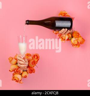 Weibliche Hand mit Maniküre gießt Champagner in ein Glas durch Ein Loch in einem zerrissenen Papier mit Rosen verziert - Stockfoto