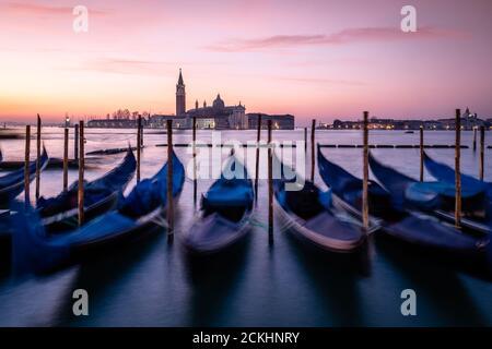 Angedockt Gondeln in der Laguna Veneta mit der Bazilika San Giorgio Maggiore im Hintergrund während des Sonnenaufgangs in Venedig, Italien