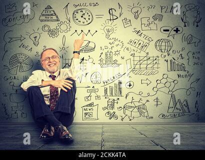 Happy Senior Business man ältere Unternehmer Lehrer sitzt auf einem Boden zeigt auf neue Projektberechnungen auf grauem Wandhintergrund - Stockfoto