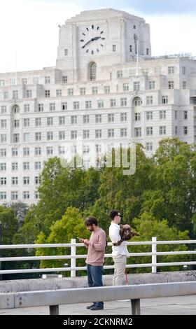 London, England, Großbritannien. Ein Mann am Telefon und ein anderer hält seinen Hund (für ein Foto) auf der Waterloo Bridge. Shell Mex House (80 Strand) dahinter - Stockfoto