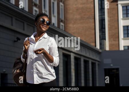 Sommer-Außenaufnahme einer fröhlichen afroamerikanischen Geschäftsfrau, die in weißem Hemd gekleidet ist, Rucksack hinter der Schulter hält und sich zum Treffen eilt - Stockfoto