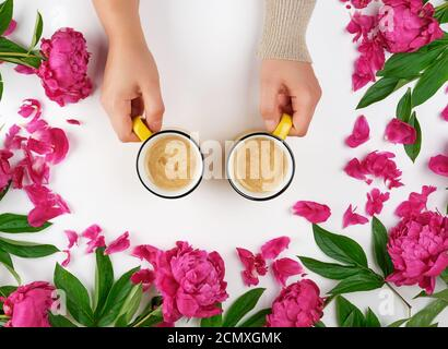 Zwei Hände halten gelbe Tassen mit einem heißen Kaffeegetränk Auf weißem Hintergrund inmitten der Blüte Stockfoto