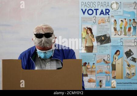 Ein Mann mit Schutzmaske bereitet eine Abstimmung vor, während die Menschen warten, um ihre Stimmen für die landesweiten Kommunalwahlen abzugeben, inmitten der Besorgnis über die Ausbreitung der Coronavirus-Krankheit (COVID-19), in einem Wahllokal in Santo Domingo, Dominikanische Republik, 15. März 2020. REUTERS/Ricardo Rojas - Stockfoto