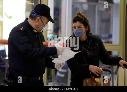 Die Polizei überprüft die Selbstzertifizierungsdokumente eines Passagiers, der mit dem Zug von Turin und Mailand zum Hauptbahnhof von Neapel kommt, da Italien die Maßnahmen zur Verlangsamung der Ausbreitung der Coronavirus-Krankheit (COVID-19) in Neapel, Italien, am 22. März 2020, verstärkt. REUTERS/Ciro De Luca