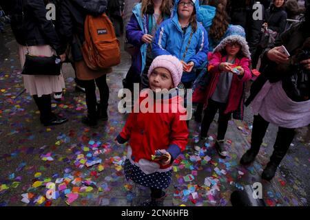 """Fußgänger halten an, um Konfetti zu fangen, während Mitglieder der Times Square Alliance einen """"Lufttüchtigkeitstest"""" für Konfetti durchführen, der dem ähnelt, was für Silvester in New York am 29. Dezember 2015 verwendet wird. REUTERS/Lucas Jackson - Stockfoto"""