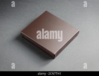 Schwarze Geschenkbox mit goldenem Band auf schwarzem Hintergrund