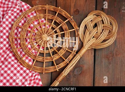 Löffel und runde Weide stehen für Töpfe auf einem braunen Holztisch