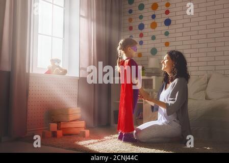 Glückliche liebevolle Familie. Mutter und ihr Mädchen spielen zusammen. Mädchen in einem Superman's Kostüm. - Stockfoto