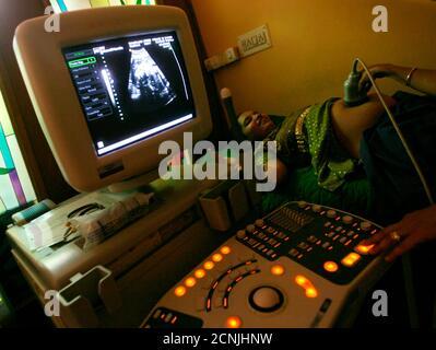 """Nayna Patel, eine indische Gynäkologe führt eine Ultraschall-Untersuchung auf Shabnam, eine Leihmutter Patel Klinik in Anand im indischen Bundesstaat Gujarat 4. März 2009. In der Klinik von Nayna Patel Surrogate von Arco vielleicht Indiens bekannteste """"Surrogat Doctor"""", Anand Stadt erste Surrogat-Baby, mehr Frauen sind Anmeldung geliefert werden, mit sogar Krankenschwestern und Lehrer Schlange, wie ihre Ehemänner ihren Arbeitsplatz verlieren. Die Frauen, die kommen, hier in der Regel das Geld ein Haus kaufen wollen zahlen, Kredite oder für ihre Kinder-College-Ausbildung, """"sagte Patel in ihre kleine Klinik, die Wände des - Stockfoto"""
