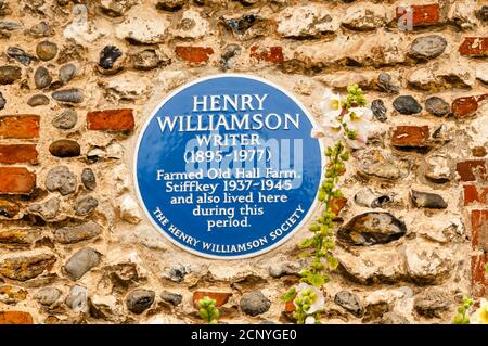Eine blaue Plakette der Henry Williamson Society auf dem Grundstück in Stiffkey, wo Williamson 1937 - 1945 bewirtschaftet und gelebt hat. - Stockfoto