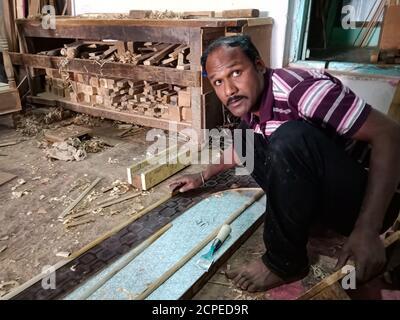 DISTRIKT KATNI, INDIEN - 08. JANUAR 2020: Ein indischer Holzkünstler, der bei der Herstellung von Möbeln in der Werkstatt auf die Kamera schaut. - Stockfoto