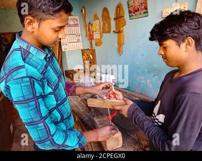 DISTRIKT KATNI, INDIEN - 08. JANUAR 2020: Zwei indische junge Arbeiter arbeiten zusammen in der Holzfabrik. - Stockfoto