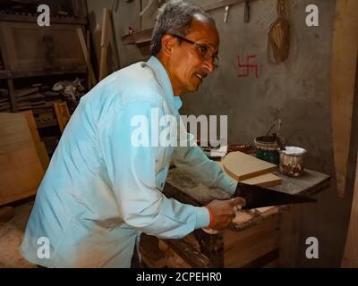 DISTRIKT KATNI, INDIEN - 08. JANUAR 2020: Ein indischer Sägefabrikarbeiter, der in der Werkstatt Holzstättenholz schneidet. - Stockfoto