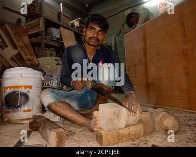 BEZIRK KATNI, INDIEN - 08. JANUAR 2020: Ein indischer Sägefabrikarbeiter hackt Holz in der Werkstatt. - Stockfoto