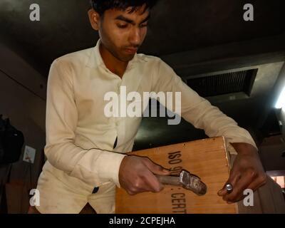 BEZIRK KATNI, INDIEN - 08. JANUAR 2020: Ein indischer Sägefabrikarbeiter hämmerte Sperrholz in der Werkstatt. - Stockfoto