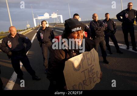 """Ein Migrant ruft Slogans, während sie während eines Protestes auf einer Autobahn in Calais, Frankreich, am 7. August 2015 ein Schild vor einer Reihe französischer Polizeibeamter hält. Für die meisten der 3,000 Einwohner des """"Dschungels"""", einer Kleinstadt an den Sanddünen der französischen Nordküste, ist der Höhepunkt eines jeden Tages der nächtliche Versuch, sich in den Unterwassertunnel zu schleichen, von dem sie hoffen, dass er zu neuem Leben in Großbritannien führen wird. REUTERS/Juan Medina"""