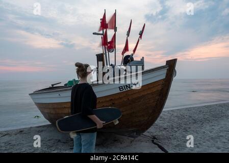 Mädchen mit Longboard steht vor einem Fischerboot - Stockfoto