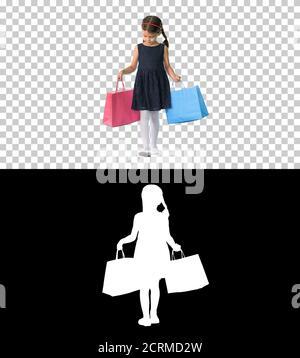 Schöne kleine Mädchen in schwarzem Kleid zu Fuß mit Einkaufstaschen, - Stockfoto