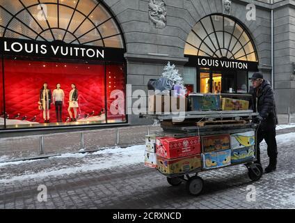 Eine Straße Verkäufer schiebt einen Wagen beladen mit waren vor einem Louis Vuitton Store in Kiew, Ukraine 5. Januar 2017.  REUTERS/Gleb Garanich - Stockfoto