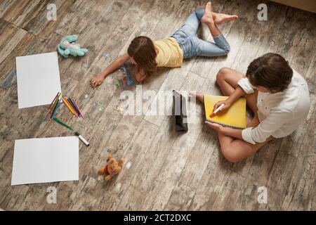 Bruder und Schwester liegen zu Hause auf dem Holzboden und verbringen Zeit miteinander. Kleines Mädchen spielt mit Puzzles, Junge mit digitalen Tablet und Stockfoto