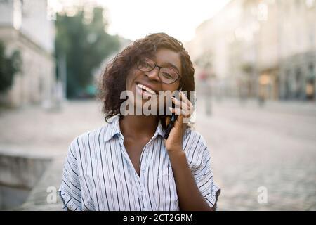 Nahaufnahme Porträt von attraktiven lockigen afrikanischen Mädchen reden auf dem Handy, Blick auf Kamera und lachen, zu Fuß im Freien auf der alten Stadtstraße an Stockfoto