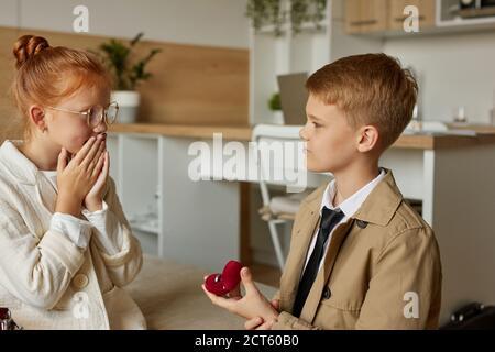 Überrascht kleines Mädchen erhalten Vorschlag von ihrem Freund, Kind Junge im Mantel stehen auf Knien vor ihr, in der Liebe. Kinder Beziehungen Konzept Stockfoto