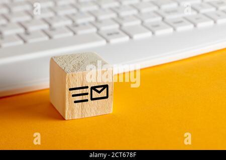 E-Mail-Symbol auf Holzblock mit Computer-Tastatur Hintergrund auf gelb. Kundenbetreuung, Support oder E-Mail-Messaging-Konzept. Stockfoto