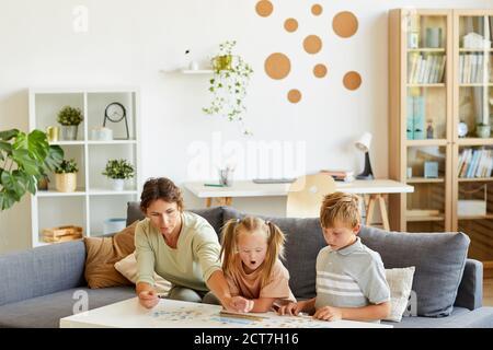 Weitwinkel-Porträt der liebevollen Familie mit besonderen Bedürfnissen Kind spielt mit Puzzles und Brettspiele zusammen zu Hause, kopieren Raum