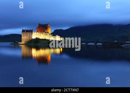 Eileen Donan Castle nach Sonnenuntergang an einem bewölkten Abend beleuchtet, West Highlands, Schottland, Großbritannien