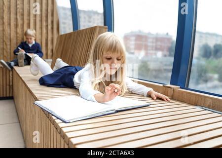 Kleines blondes Mädchen A schreibt eine romantische Note zu einem Jungen. Im Hintergrund ein Junge in Unschärfe