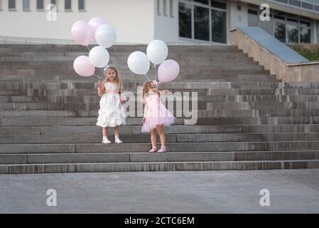 Zwei kleine Mädchen in rosa und weißen Kleidern mit Luftballons Zu Fuß auf der Straße - Stockfoto