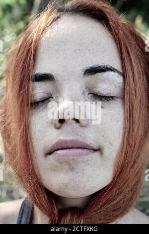 Nahaufnahme Porträt einer roten Haare Frau Mädchen mit Sommersprossen. Porträt eines Mädchens im Freien im Sonnenlicht. Geschlossene Augen Stockfoto