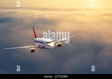 Das Flugzeug fliegt im Sommer bei Sonnenuntergang über den Wolken