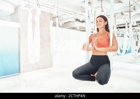 Junge schöne und glückliche Fitness-Frau in Sportkleidung sitzen in Lotus Pose in weiß hängenden Hängematte und meditieren, tun fliegen Yoga. Wellness und gesunde Lebensweise, Harmonie leben - Stockfoto