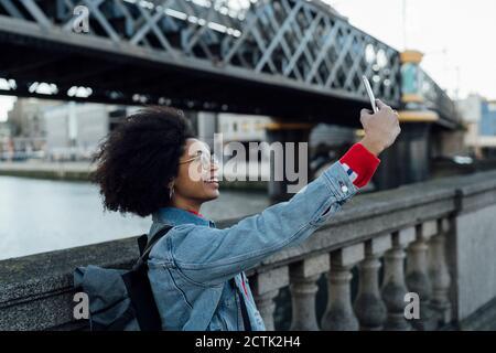 Afro junge Frau nimmt Selfie mit Smartphone im Stehen Durch Geländer in der Stadt - Stockfoto