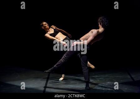 Männliche und weibliche Tänzerin, die zeitgenössisches Ballett auf schwarzer Bühne aufführt Stockfoto