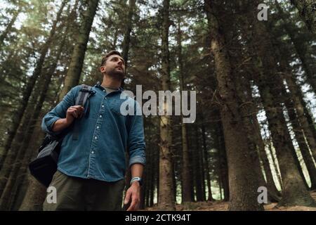 Mittelerwachsener Mann, der beim Stehen gegen Bäume im Wald kontempliert