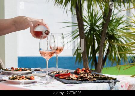 Eine Hand der Frau Gießen Roséwein während einer Familienfeier eines Mittagessens. Lifestyle-Konzept - Stockfoto